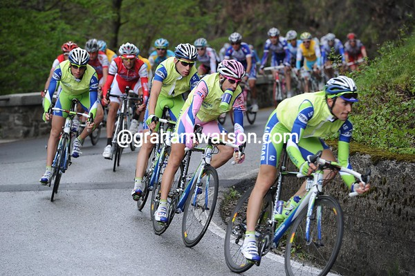 The descent is slick with rain and dirt - Basso leads Nibali through a turn...