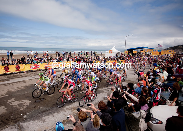 The peloton rolls out under sunny skies from San Francisco...