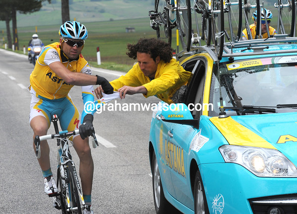 Jufre and Stangelj have dropped out of the escape to help Astana chase, but Jufre is frozen after waiting - a mechanic tries to dress him in dry clothes...