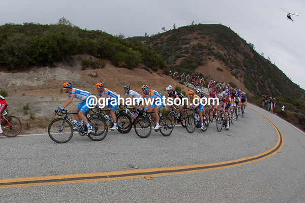 A light rain is now falling as the peloton enters a hairpin turn.