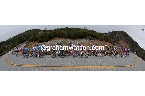 Zabriskie and the peloton snake through a series of turns. <br><br><font size=-1>*note - if purchased, this print will have white areas as shown above, you can trim to fit your panoramic frame.</font>