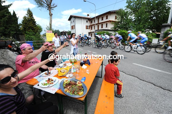 Italian fans cheer the Giro peloton while enjoying a roadside lunch, with wine from Friuli...