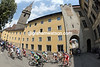 The peloton squeezes out of the historic centre of Brunico towards the official start...