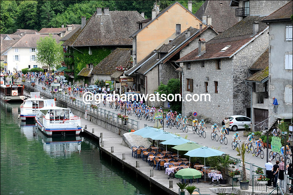 The peloton is still led by Garmin as it passes through the pretty riverside town of Vions...