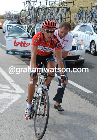 Philippe Gilbert makes a wheel-change and gets a push ffrom team manager, Marc Sergeant...
