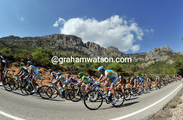 The familiar rocky spires of Confrides look down on the peloton as it stretches out in pursuit...