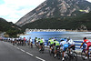 The peloton sights the Pyreness as it circles a massive reservoirwith 60-kilometres to go...