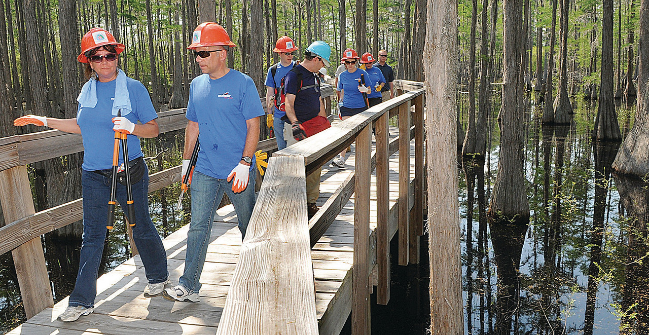 Southwest Airlines employees cross a lake while helping clear a portion of the Florida Trail at Pine Log State Forest near Ebro on Sunday.