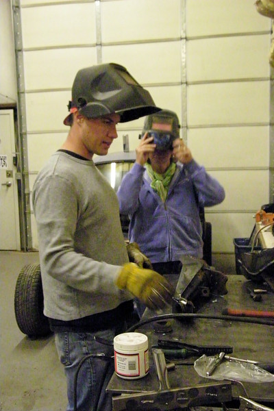 Josh is showing Kris how to weld.