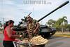 Nicaragua - Managua : Desfile militar como parte de la conmemoracion del 32 aniversario del ejercito nacional . maiz tostado. Carro de combate. / Nicaragua's Army celebrates its 32nd anniversary. A soldier buys from a sidewalk vendor roasted corn. / Nikaragua: Militärparade zum 32. Jahrestag der nicaraguanischen Revolution in Managua. Ein Soldat kauft von einer Strassenhändlerin gebratene Maiskolben. © Inti Ocon/LATINPHOTO.org