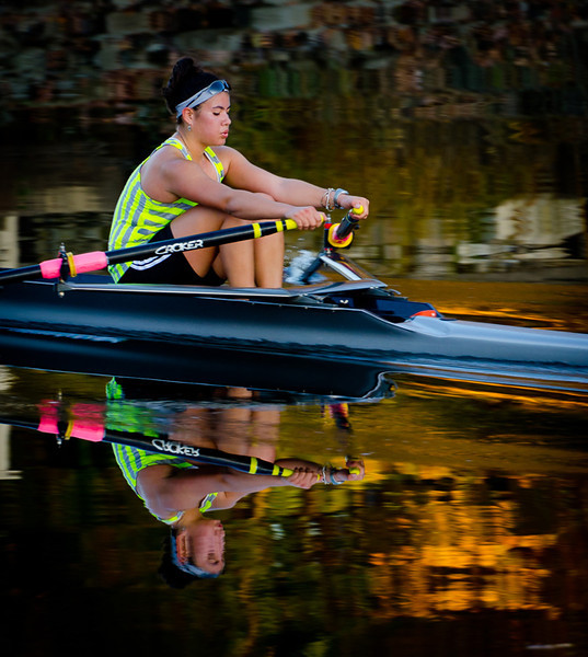 """""""Autumn Sculler"""" -- this is sort of a miracle shot. I was hand-holding my very heavy 70-200 2.8 lens with camera --  just shooting some reflections in the river when she quietly appeared around the corner moving quickly across the water-- over 100 ft from me.  I shot several times and caught her in sharp focus, taking her breaths. (see the next page for the last shot)."""