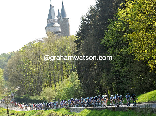 The peloton is in full flight as it passes a Chateau on the finishing lap back to Huy...