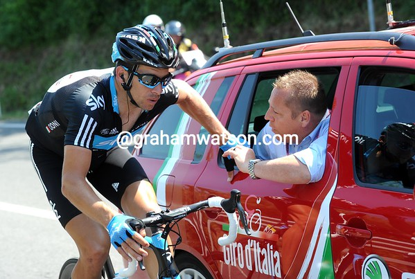 Dario Cioni is discussing the Zoncolan stage with the race's head official - some technical issues have raised concerns in the peloton...