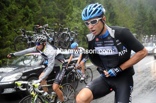 Matthew Wilson pulls on his rain jacket as the heavens open on the peloton...