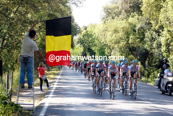 An Italian fan waves a Belgian flag as a tribute the the grieving peloton...