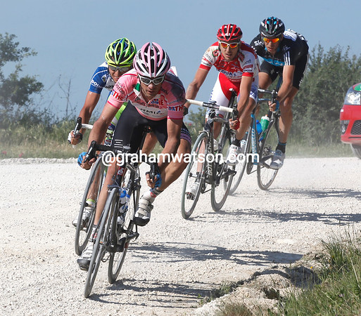 Millar has fallen on the gravel roads but chases back eventually...