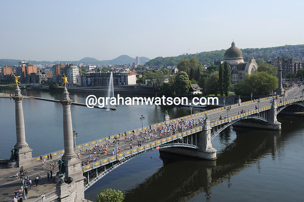 The peloton crosses the River Meuse on its way to the Ardennes...