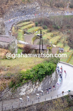 The bedraggled peloton turns off the bigger roads to commence the climbs - no-one has escaped yet...