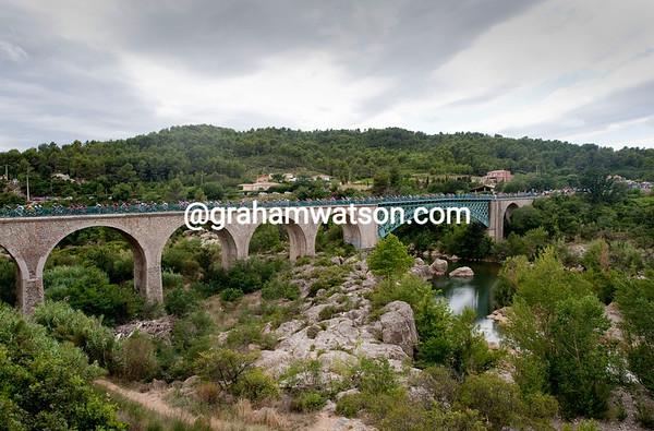 The peloton crosses a bridge in the Minervois wine region...