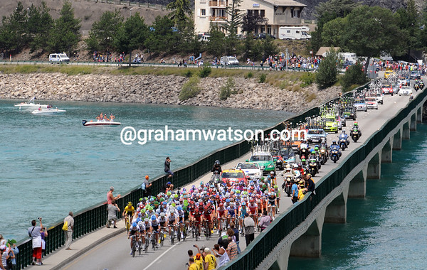 The peloton is led by Garmin over the bridge of Lac Serre-Poncon - there's an escape in front that they don't like...