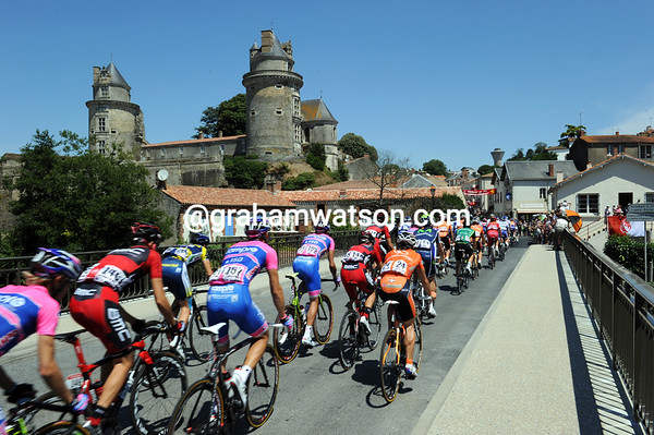 The peloton crosses the bridge and passes the Chateau at Aprimont...