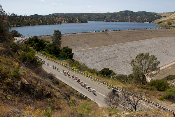 The peloton is strung out from the descent after the last KOM as it crosses a resivoir dam.
