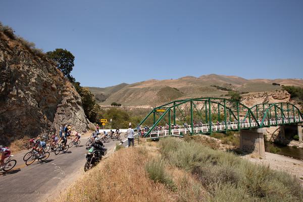 The peloton seems to be enjoying the scenery as they cross a bridge.