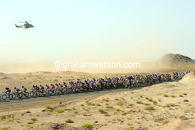 A curious observer in a military helicopter gets a bit too close to the peloton, blowing sand all over the place...