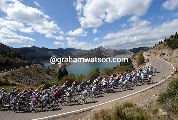The peloton slows after the feed-zone - just in time to enjoy this view of a reservoir at Paublaura de Luna...