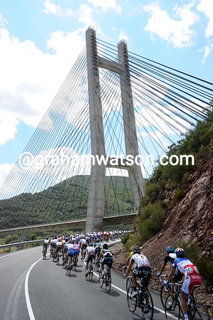 The peloton is riding at full-speed again, as they pass beneath a spectacular bridge in Castilla y Leon...