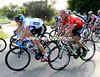 Chris Froome has a well-built man in red sitting on his wheel and watching him...