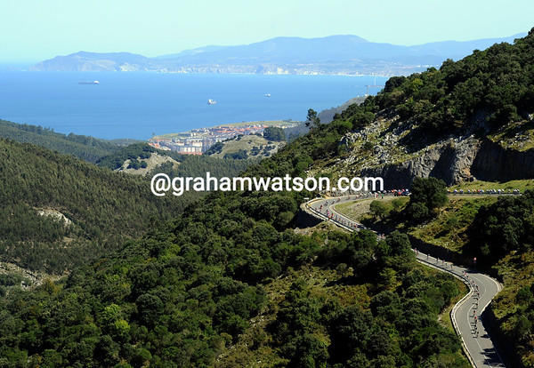 With views over the Bay of Biscay, the peloton descends the Puerto de la Granja five minutes behind the escape...