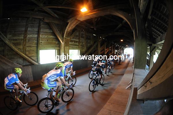 The peloton traverses an ancient wooden bridge across the Rhine...