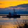 "Tugboat ""Seaspan Corsair"" heading down the Fraser River at dusk."