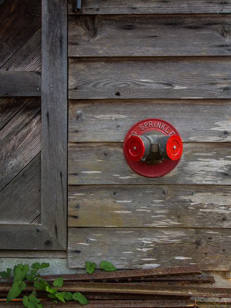 Wooden building with a contrasting red sprinkler.