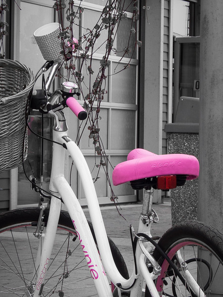 A curvey bike with pink accents.