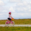 Girl with pink bicycle enjoys a sunny day in Garry Point Park.