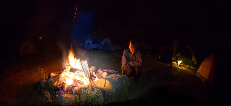Shalimar enjoys the warmth of the campfire on the bank of the American River.