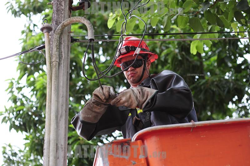 BRASIL 2012-03-29 FUNCIONARIO DA CONCESSIONARIA EDP BANDEIRANTE EQUIPE DE LINHA VIVA FAZ REPARO NAS INSTALACOES ELETRICAS EM SAO JOSE DOS CAMPOS - SP DEVIDO AS CHUVAS DE ANTEONTEM. SAO JOSE DOS CAMPOS - SP BRASIL. / A worker with hard hat and safety glasses repaired a cable from an electric pole. / Brasilien: Reparatur von elektrischen Leitungen. Schutzhelm. Kran. © Lucas Lacaz Ruiz/LATINPHOTO.org