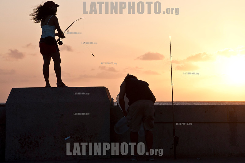 Cuba: Una pareja pesca en el Malecon de la Habana. / A couple fish in Havana´s Malecon (water front). / Kuba: Frau fischt neben einem Liebespaar am Malecon in Havanna. © Ariel Levi/LATINPHOTO.org
