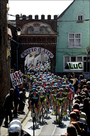 The peloton has slowed on its second passage through the town of Cassel...