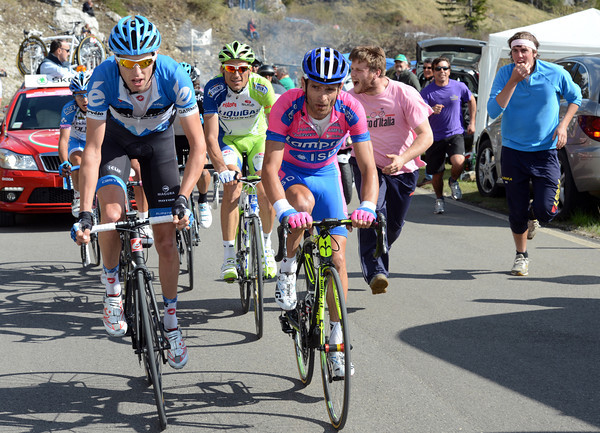 Hesjedal is riding ahead of Scarponi as some Italian fans cheer Basso on...