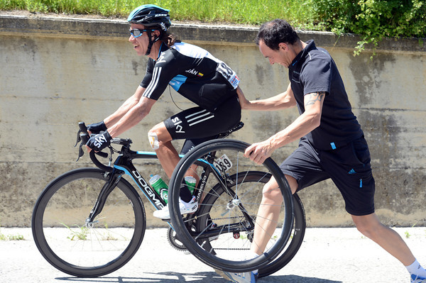 Rigoberto Uran has time to laugh as his mechanic changes a wheel...