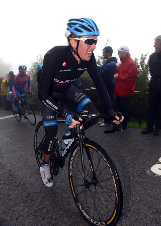 Dan Martin is further back, looking cold and miserable in the rain and fog...