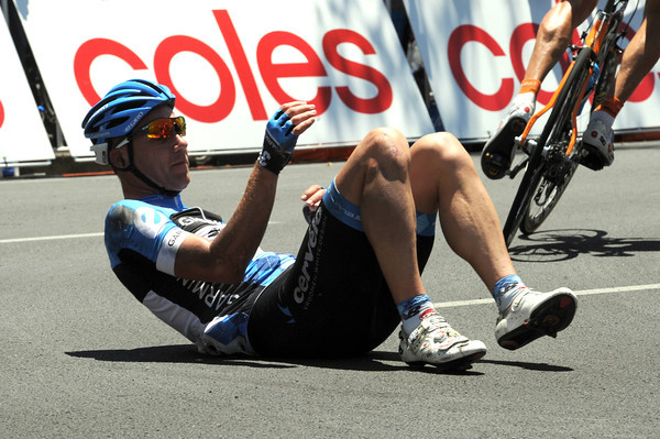 Andreas Klier falls to the ground after touching wheels on a corner...