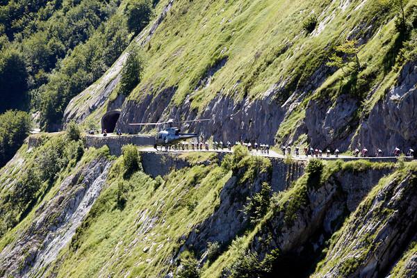 A TV helicopter films the Tour as it descends towards the Col du Soulor via a series of unique tunnels cut through the rock...