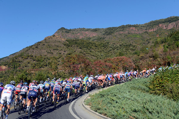 The peloton starts the final climb with the colours of early-Autumn almost camouflaging their jerseys...