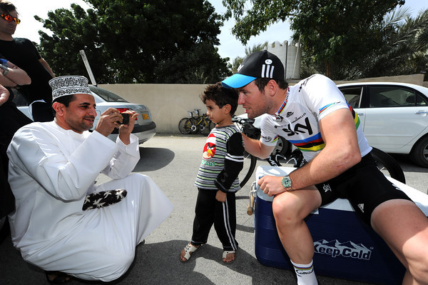 The locals are out in force at the start - Mark Cavendish obliges an Omani man and his son with a photo...