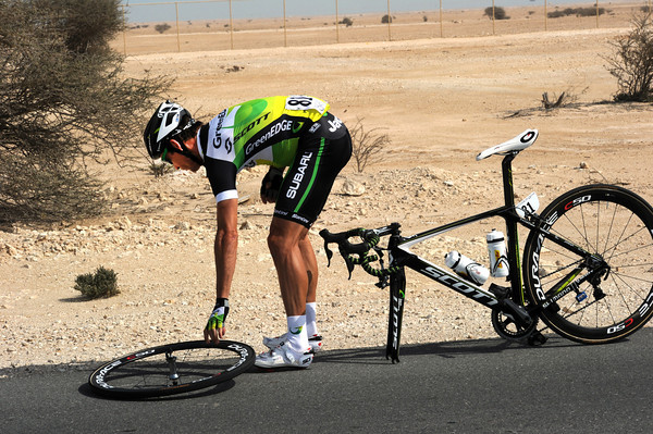 Robbie McEwen gets his front wheel out to help speed up his mechanic's work...