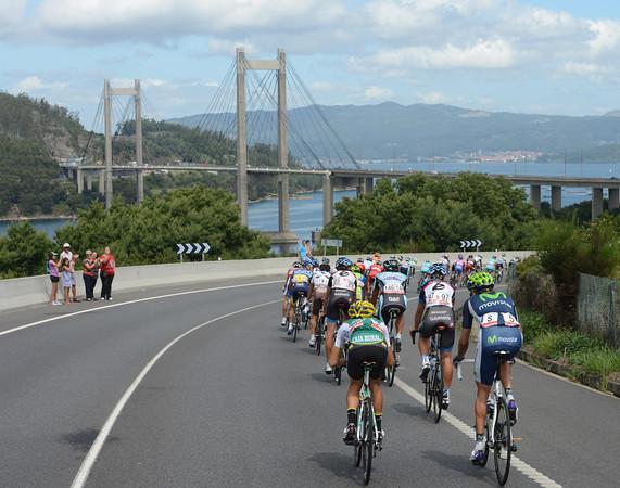 The peloton heads north along the coast, passing under the famous Ponte de Rande...